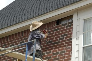Man removing brick over porte-cochere